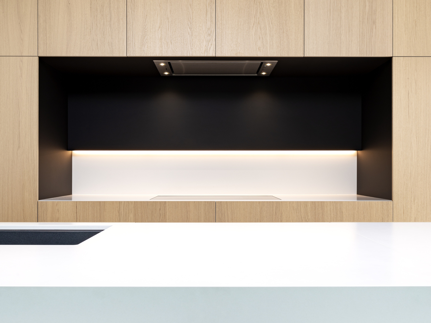 Keuken met eik fineer deuren witte en zwarte accenten inductievuur gelinkt aan dampkap